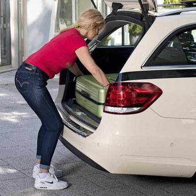 Taxifahrerin lädt Koffer in Kofferraum