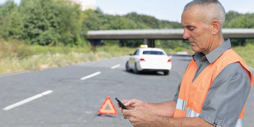 Taxifahrer mit Mobiltelefon in der Hand bei Panne