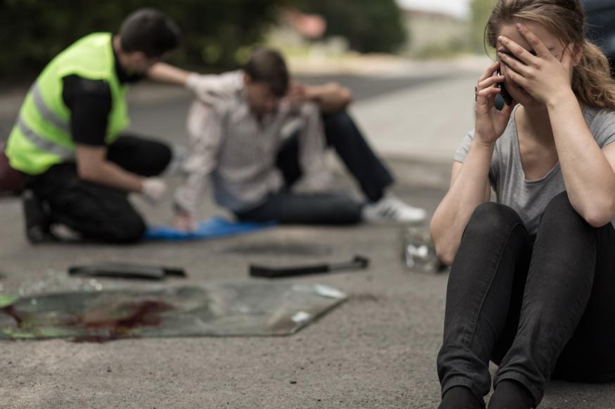 Frau telefoniert weinend nach Unfall, Ersthelfer im Hintergrund mit Verletztem