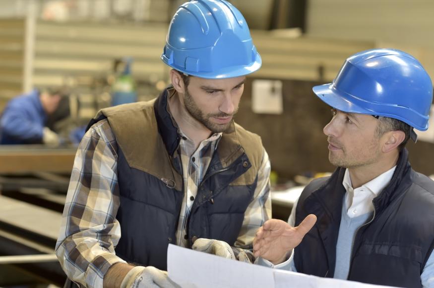 Eine Führungskraft bespricht mit einem Mitarbeiter eine Aufgabe