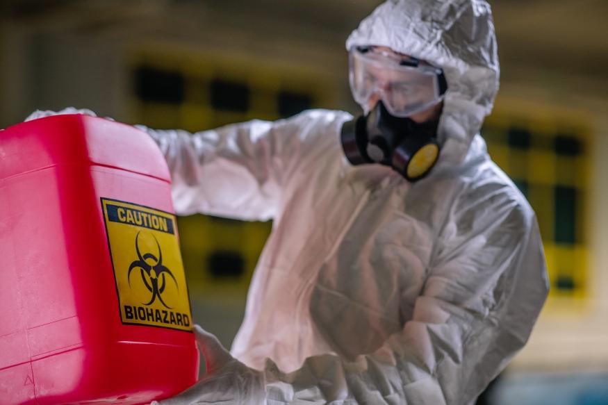 Person im Schutzanzug hält Kanister mit Aufdruck Biohazard vor sich.