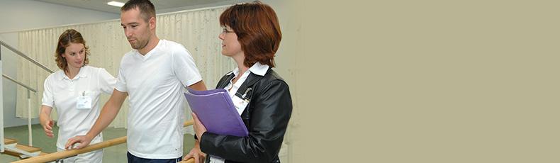 Rehamanagerin schaut Reha-Patient bei Übung zu