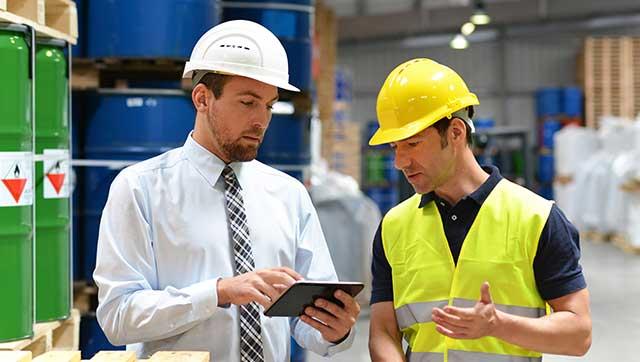 Chef und Mitarbeiter diskutieren miteinander mit Blick auf ein Tablet