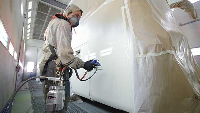 Person in Schutzausrüstung besprüht eine Wand