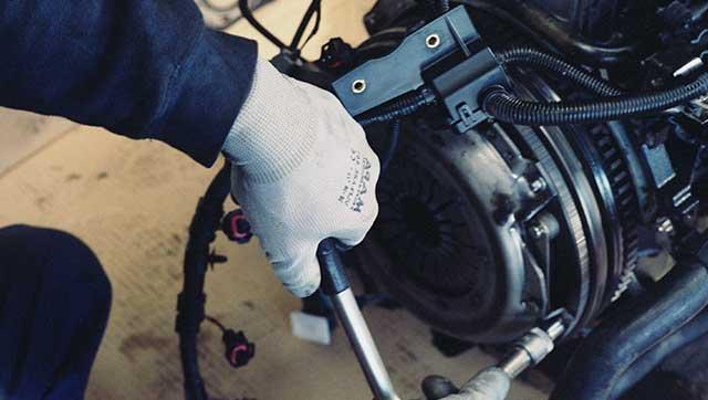 Person betätigt mit Schutzhandschuh eine Maschine