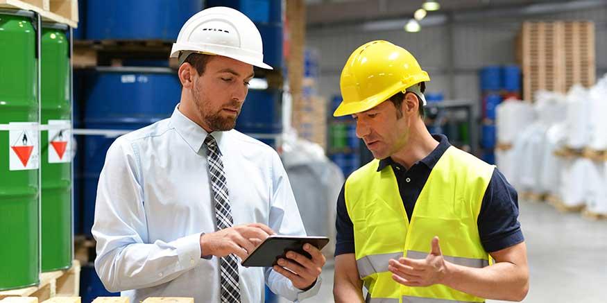 Chef und Mitarbeiter diskutieren mit Blick auf ein Tablet