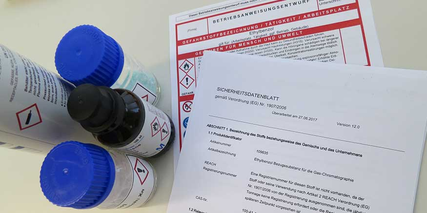 kleine Behälter mit Gefahrstoffen stehen neben Sicherheitsdatenblatt