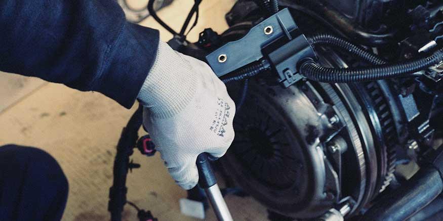 Hand im Schutzhandschuh greift Gerät