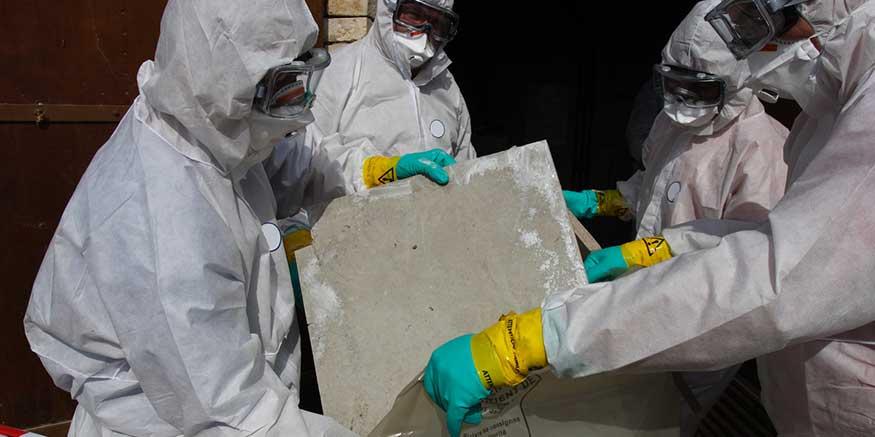 Arbeiter in Schutzanzügen bei der Entsorgung von asbesthaltigem Baumaterial