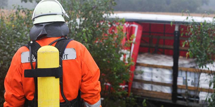 Feuerwehrmann blickt auf offene Lkw-Ladung