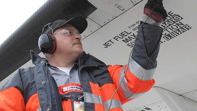 Flughafenmitarbeiter mit Gehörschutz arbeitet an Luftfahrzeug