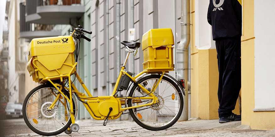 Postbote neben seinem Fahrrad