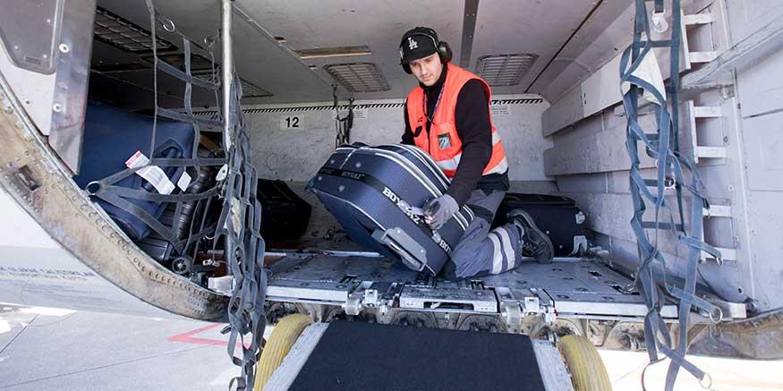 Mitarbeiter Bodencrew hebt Gepäck aus Flugzeug