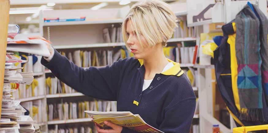 Mitarbeiterin sortiert Broschüren in Regal ein