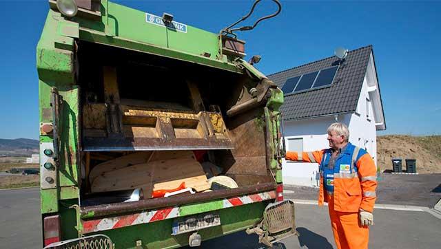 Müllwerker bedient Müllpresse