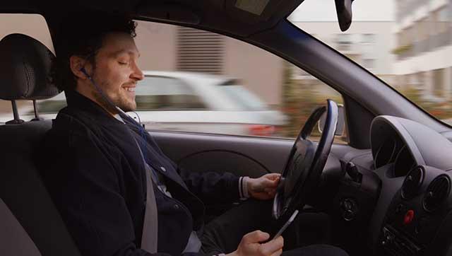Fahrer hält Smartphone am Steuer in der Hand