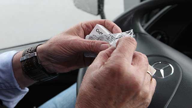 Fahrer öffnet Medikamentenschachtel hinterm Steuer