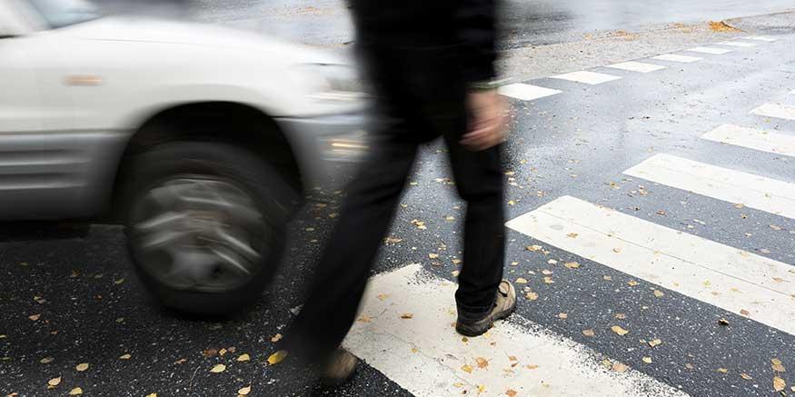 Person geht vor einem Auto über den Zebrastreifen