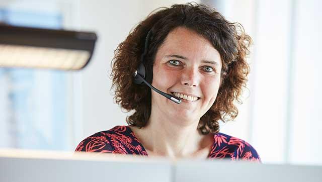 Frau mit Headset lächelt hinter Bildschirmen hervor