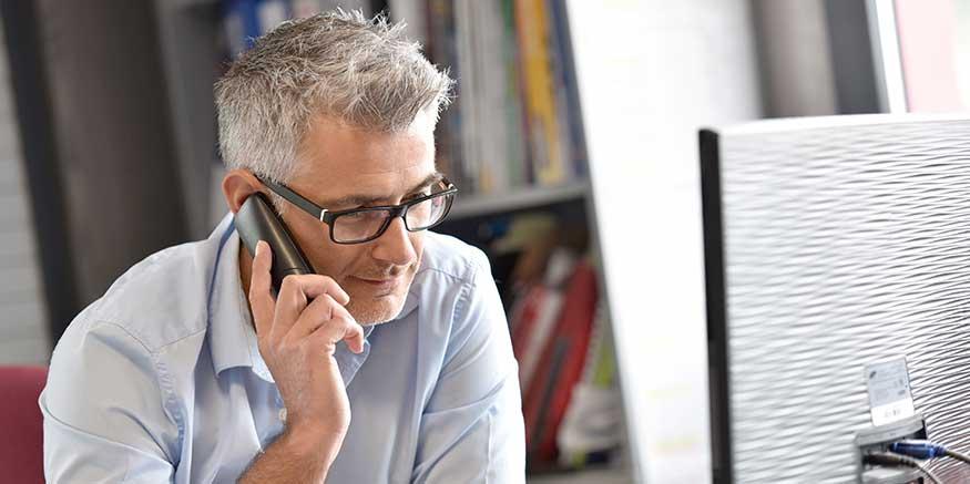 Mann hält Telefonhörer