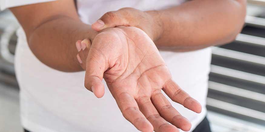 Mann umfasst sein schmerzendes Handgelenk